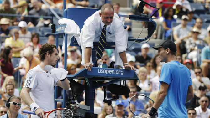 Britain's Andy Murray, left, and Czech Republic's Tomas Berdych, right, talk with the umpire about a call during a semifinal match at the 2012 US Open tennis tournament,  Saturday, Sept. 8, 2012, in New York. (AP Photo/Darron Cummings)