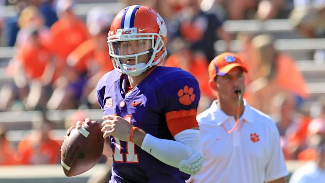 Clemson quarterback Chad Kelly, left, runs a play in front of head coach Dabo Swinney, right, during an NCAA college football spring game at Memorial Stadium in Clemson, S.C., Saturday, April 12, 2014. (AP Photo/Anderson Independent-Mail, Mark Crammer) GREENVILLE NEWS OUT; SENECA NEWS OUT