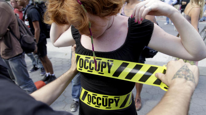 """""""Occupy"""" security-style tape is stuck to Laura Nagy during an Occupy Wall Street anniversary concert in Foley Square in New York on Sunday, Sept. 16, 2012. The Occupy Wall Street movement will mark its first anniversary on Monday. (AP Photo/Seth Wenig)"""