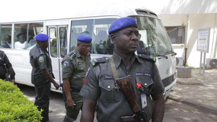 Security men stand guard in front of a bus conveying All progressives Congress opposition governors after visiting victims of at the Accident and Emergency unit of Asokoro hospital where injured people from Monday's explosion at a bus station are receiving treatment in Abuja, Nigeria, Wednesday, April 16, 2014. Scores of peopledied in the the blast that destroyed more than 30 vehicles and caused secondary explosions as their fuel tanks exploded and burned. The Monday attack just miles from Nigeria's seat of government increases doubts about the military's ability to contain an Islamic uprising that is dividing the country on religious lines as never before. (AP Photo/ Sunday Alamba)