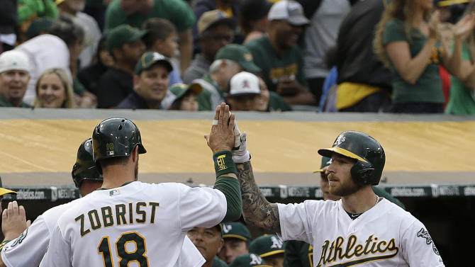 Oakland Athletics' Ben Zobrist (18) is congratulated by Brett Lawrie (15) after scoring during the first inning of a baseball game against the Seattle Mariners in Oakland, Calif., Thursday, July 2, 2015. (AP Photo/Jeff Chiu)