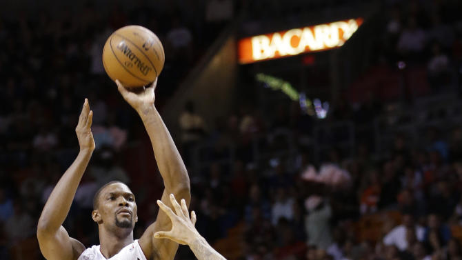 Miami Heat center Chris Bosh (1) shoots against New York Knicks center Tyson Chandler during the first half of an NBA basketball game, Tuesday, April 2, 2013 in Miami. (AP Photo/Wilfredo Lee)