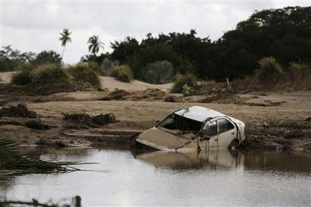 A car lies partially submerged in floodwater at the golf course of a hotel in the flooded Mexican beach resort of Acapulco