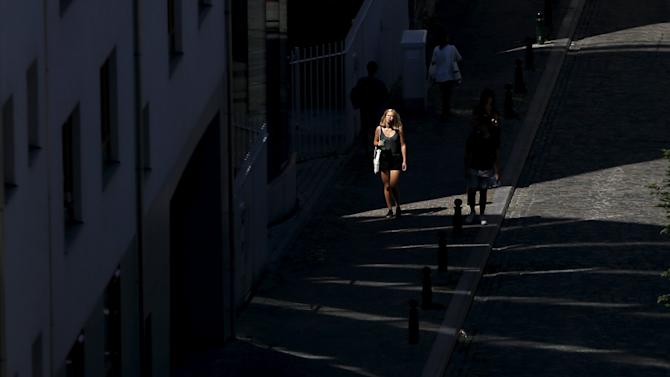 A woman walks up a street on a hot summer day in the Marolles district in Brussels