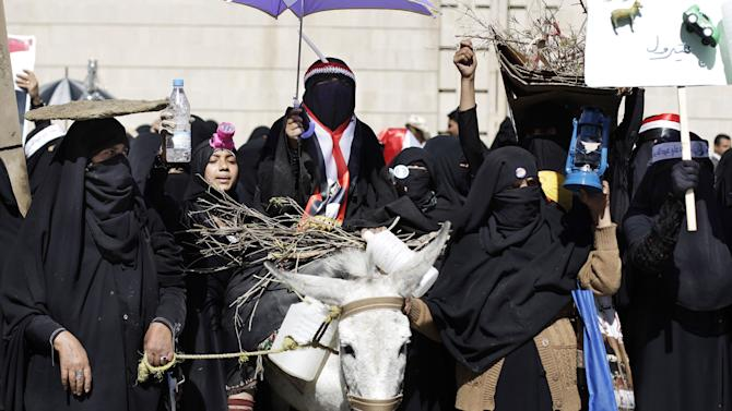 "A female supporter, center, of Yemen's President Ali Abdullah Saleh rides a donkey during a rally demanding basic services from the new government in Sanaa, Yemen, Monday, Jan. 9, 2012. Arabic writing on the placard, far right, reads, ""petrol."" (AP Photo/Hani Mohammed)"