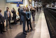 French Prime Minister Jean-Marc Ayrault (centre) at the Luxembourg station in Paris as he awaits a suburban train on Paris' Regional Express Network (RER) line B while campaigning for Sunday's parliamentary elections