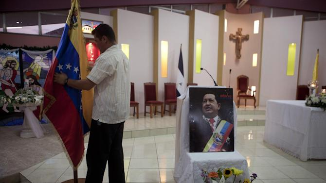 """A man prepares a Venezuelan flag next to an image of Venezuela's President Hugo Chavez before a mass in support of him in Managua, Nicaragua, Wednesday Dec. 12, 2012. Venezuela's Information Minister Ernesto Villegas expressed hope about Chavez returning home for his Jan. 10 swearing-in for a new six-year term after his cancer surgery in Cuba, but said in a written message on a government website that if Chavez doesn't make it, """"our people should be prepared to understand it."""" (AP Photo/Esteban Felix)"""
