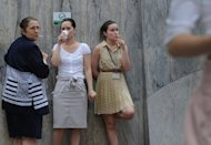 "Romanian women smoke outside the headquarters of a bank in Bucharest in June 2011. The World Health Organization warns that tobacco use could kill a billion people or more over the course of the 21st century ""unless urgent action is taken"