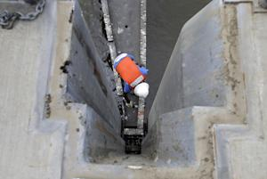 A worker secures a flood gate after a crane lowered…