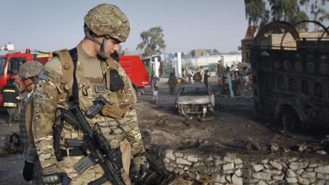 An unidentified U.S. soldier is seen at the scene of a suicide attack in Jalalabad, Nangarhar province, east of Kabul, Afghanistan on Wednesday, May 18, 2011. Afghan officials say at least 10 people have been killed in a bomb attack on a police bus that was carrying people to a police academy in eastern Afghanistan. (AP Photo/Rahmat Gul)