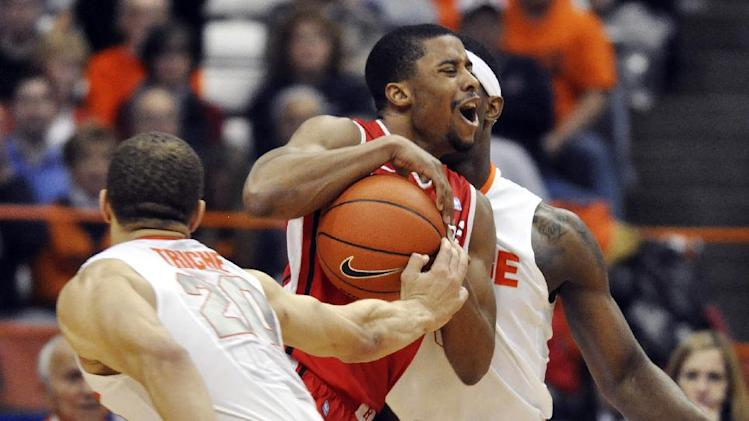 Rutgers' Jerome Seagears tries to dribble through Syracuse's Brandon Triche, left, and C. J. Fair during the second half of an NCAA college basketball game in Syracuse, N.Y., Wednesday, Jan. 2, 2013. Syracuse won 78-53. (AP Photo/Kevin Rivoli)