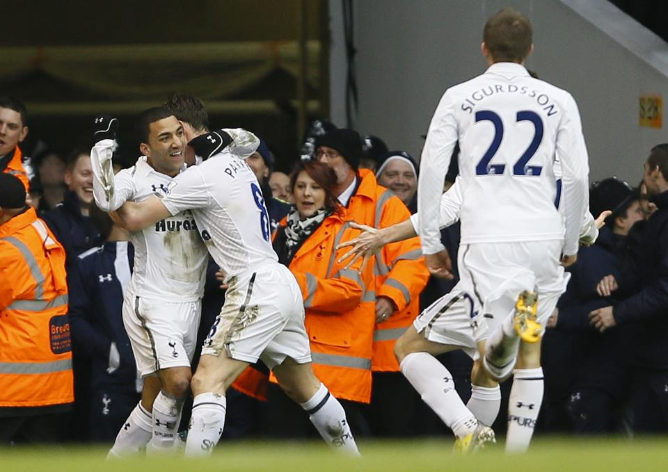 Tottenham Hotspur's Aaron Lennon, left, is embraced by teammate Scott Parker as he celebrates with teammates after scoring a goal against Arsenal during the English Premier League soccer match between Tottenham and Arsenal at Tottenham's White Hart Lane stadium in London, Sunday, March  3, 2013. (AP Photo/Kirsty Wigglesworth)
