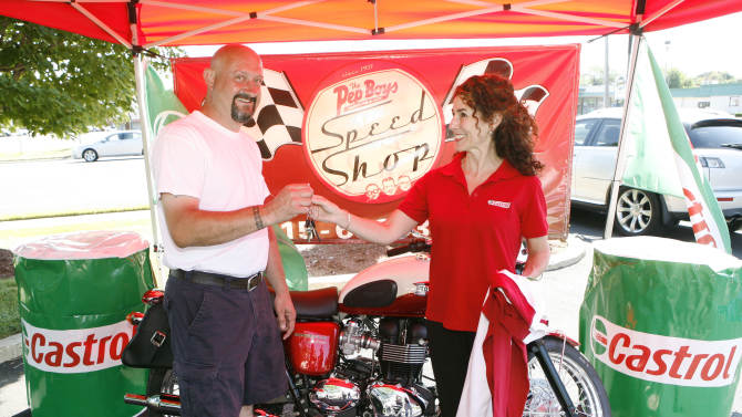 COMMERCIAL IMAGE - In this photograph taken by AP Images for Castrol, Allison Billingsby, Castrol Trade Marketing Manager, hands Fred Diehl, Castrol Triumph Sweepstakes winner, the keys to his new Triumph Bonneville T100 at a Pep Boys in Bensalem, Pa. Saturday, June 23, 2012. (Mark Stehle/AP Images for Castrol)