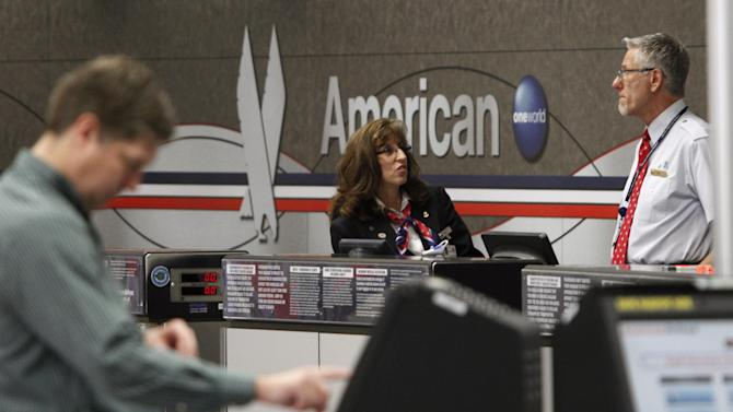 American Airlines counter agents chat as a customer uses a self check kiosk at Dallas-Fort Worth International airport in Grapevine, Texas, Wednesday, Feb. 1, 2012. American Airline corporate leadership is having closed door meetings with union representatives about the future of jobs and the pension for workers. (AP Photo/LM  Otero)(AP Photo/LM  Otero)