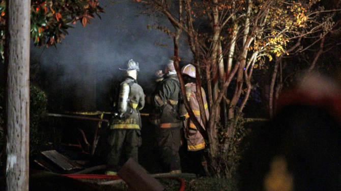 Fire fighters re-enter a west Jackson, Miss., home where authorities say a small plane carrying three people crashed shortly after 5 p.m. Tuesday evening, Nov. 13, 2012. The home's resident is believed to have escaped but authorities have not released names of plane's passengers.  (AP Photo/Rogelio V. Solis)