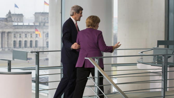 German Chancellor Angela Merkel, right, United States Secretary of State John Kerry on the way to Merkel's office after a statement for media prior to a meeting at the chancellery in Berlin, Tuesday, Feb. 26, 2013. Berlin is the second stop in Kerry's first trip overseas as Secretary of State. (AP Photo/Markus Schreiber)