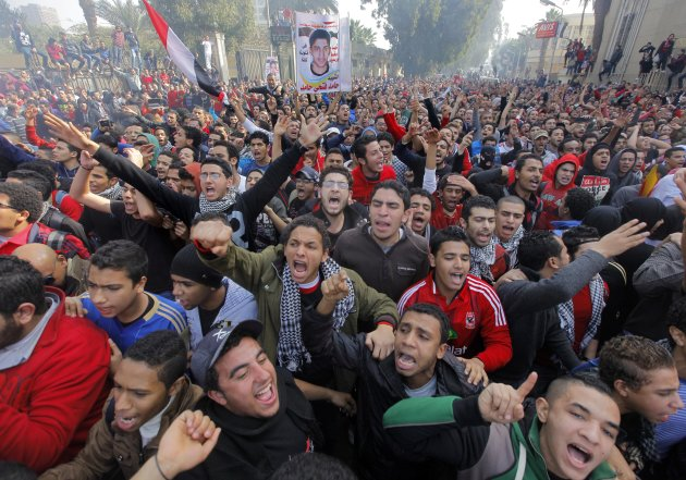 "Egyptian soccer fans of Al-Ahly club celebrate in front of their club in Cairo, Egypt, Saturday, Jan. 26, 2013. An Egyptian court sentenced 21 people to death on charges related to one of the world's deadliest incidents of soccer violence, which killed 74 mostly teenage fans of Egypt's most popular sports club last year. Poster in background showing one of the victims with Arabic reads ""martyr Hamed Fathi Hamed."" (AP Photo/Amr Nabil)"