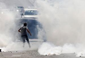 A Palestinian protester runs from tear gas fired by …