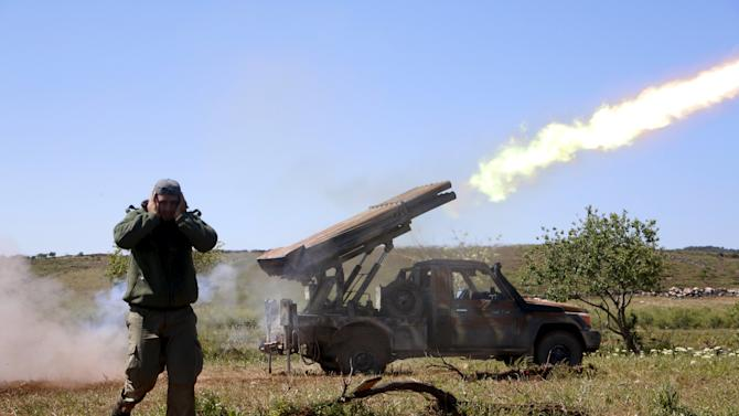 A rebel fighter from Ahrar al-Sham Islamic Movement reacts as they fire grad rockets from Idlib countryside, towards forces loyal to President Assad stationed at Jureen town in al-Ghab plain in the Hama countryside
