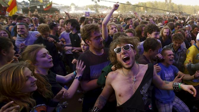 Revelers dance as they listen to the music in front of the main stage during the 21st Woodstock Festival in Kostrzyn-upon-Odra
