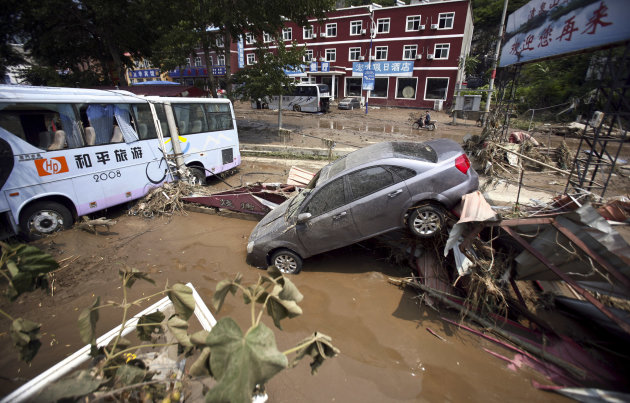 In this Tuesday July 24, 2012 photo, vehicles damaged in a flood pile up off road in Yesanpo Scenic Zone, a resort near the capital Beijing, in Laishui county, in northern China&#39;s Hebei province. The Peoples Daily newspaper says Beijings mayor and a vice mayor have resigned in what is likely a routine reshuffling but which comes amid public questioning of the governments handling of rainstorms that left at least 37 dead in the capital. (AP Photo) CHINA OUT