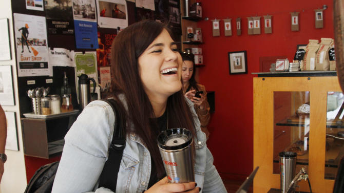 """IMAGE DISTRIBUTED FOR THERMOS - Alessa Bell receives her """"free fill"""" of coffee on the inaugural """"National Fill Your Thermos Brand Bottle Day,"""" May 23, 2013 at Contraband Coffee Bar in San Francisco. This event is being held in select cities and coffee shops throughout the nation, hosted by the iconic Genuine Thermos Brand, to kick off the holiday weekend.  (Photo by George Nikitin/Invision for Thermos/AP Images)"""