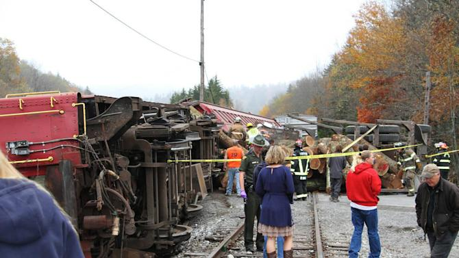 In this photo provided by the Pocahontas Times, crews work at the site where a truck carrying logs down Cheat Mountain on U.S. Route 250 crashed into the side of the train taking passengers on a scenic tour in rural Randolph County, W.Va., on Friday, Oct. 11, 2013. The crash killed one person and injured more than 60 others, according to emergency services officials. (AP Photo/The Pocahontas Times, Geoff Hamill)