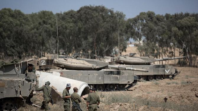 Israeli soldiers stand next to their tanks in an army deployment area near the border with the Gaza Strip on July 6, 2014 after more than 135 rockets hit Israel over the past 24 days