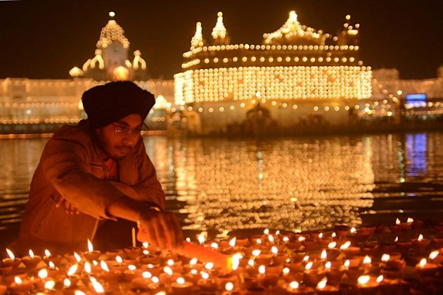 An Indian Sikh devotee lights oil lamps at the Golden Temple in Amritsar on November 13, 2012, on the ocassion of Bandi Chhor Divas or Diwali. Sikhs celebrate Bandi Chhor Divas or Diwali to mark the r