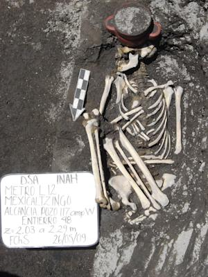 In this May 26, 2009 image released by Mexico's National Institute of Anthropology and History (INAH), the skeleton of a person lies next to an incense holder after it was found during excavations for the newest line 12 of the subway in Mexico City. The institute says several Aztec offerings were found during the construction of the subway line performed between 2008 and 2011, and announced it on Tuesday Dec. 31, 2013. (AP Photo/INAH)