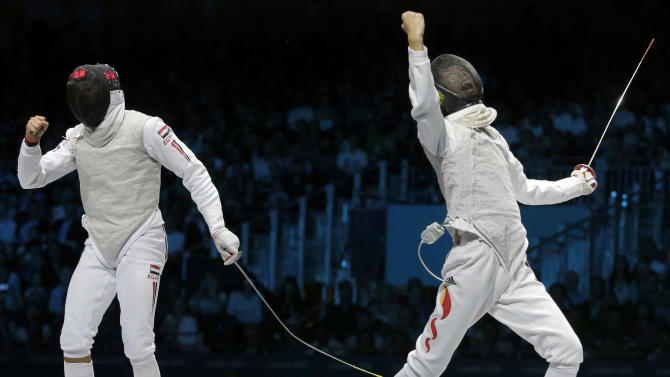 Lei Sheng of China, left, and Alaaeldin Abouelkassem of Egypt, react during their men's individual foil fencing gold medal match at the 2012 Summer Olympics, Tuesday, July 31, 2012, in London. Lei won. (AP Photo/Dmitry Lovetsky)