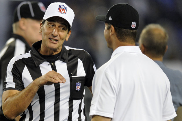 Referee Gene Steratore, left, talks with Baltimore Ravens head coach John Harbaugh before an NFL football game between the Ravens and the Cleveland Browns in Baltimore, Thursday, Sept. 27, 2012. (AP Photo/Nick Wass)