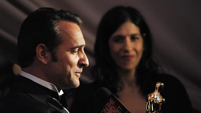 """Jean Dujardin winner of best actor for this work in """"The Artist"""" looks at his Oscar award at the Governors Ball following the 84th Academy Awards on Sunday, Feb. 26, 2012, in the Hollywood section of Los Angeles. (AP Photo/Chris Pizzello)"""