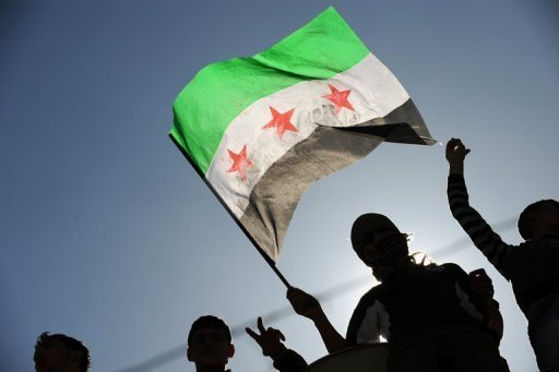 Syrian refugees wave the Free Syrian flags at the Yayladagi refugee camp in Antakya -- on the Turkish-Syrian border -- in April 2012. The number of Syrian refugees registered in Turkey has topped 30,000, a Turkish foreign ministry official has told AFP