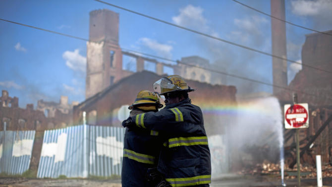 Firefighters greet each other in the aftermath of a fire in a warehouse on York Street near Kensington Avenue in Philadelphia on Monday, April 9, 2012. Two firefighters died after a wall collapsed on them while they fought the massive early-morning blaze. (AP Photo/Matt Rourke)