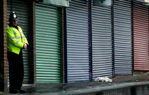 <p>A policeman stands beside a row of closed shops in Birmingham.</p>