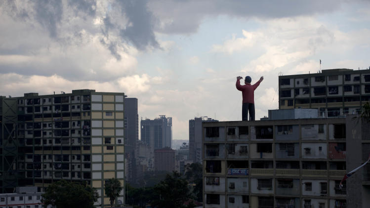 FILE - In this Oct. 6, 2012 file photo, a giant inflatable doll representing President Hugo Chavez stands on top of a building in Caracas, Venezuela. After four election wins, Chavez is on track to completing at least 20 years in power. (AP Photo/Ramon Espinosa, File)
