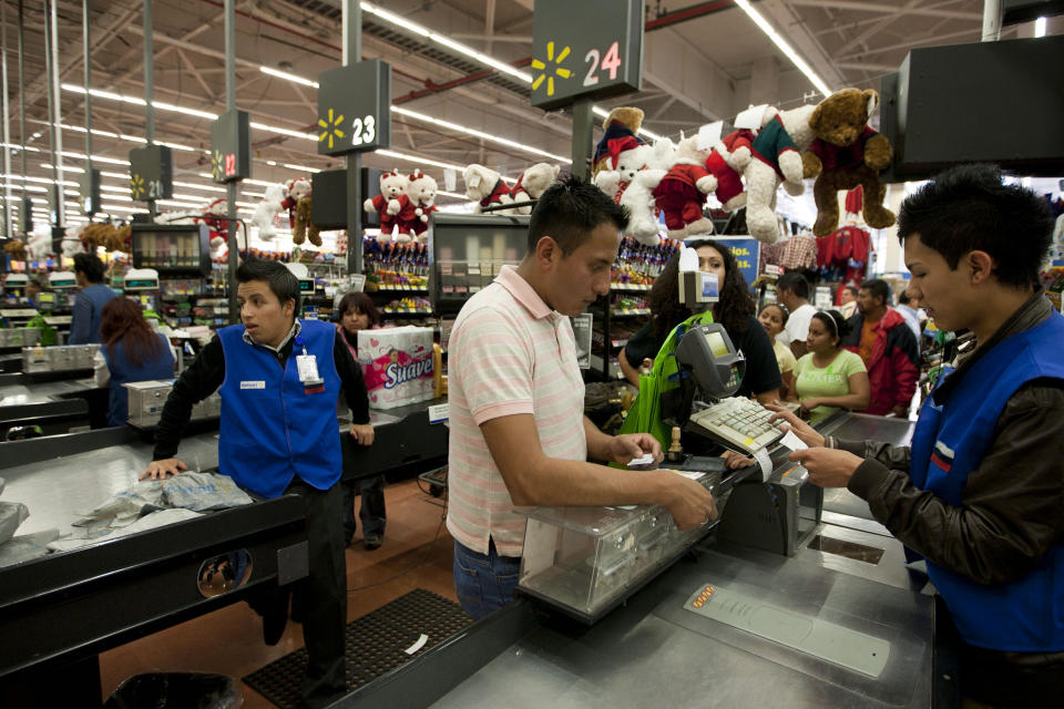 In this Nov. 18, 2011 photo, a man pays at the cash register at a Wal-Mart Superstore in Mexico City. Wal-Mart Stores Inc. hushed up a vast bribery campaign that top executives of its Mexican subsidiary carried out to build stores across Mexico, according to a published report by the New York Times. (AP Photo)