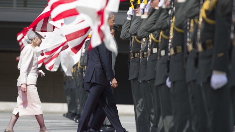 President Barack Obama, center, walks with Japanese Emperor Akihito, behind president Obama, and his wife Empress Michiko, left, past a line of flags as he arrives for a welcome ceremony at the Imperial Palace in Tokyo, Thursday, April 24, 2014. Facing fresh questions about his commitment to Asia, Obama will seek to convince Japan's leaders Thursday that he can deliver on his security and economic pledges, even as the crisis in Ukraine demands U.S. attention and resources elsewhere. (AP Photo/Carolyn Kaster)