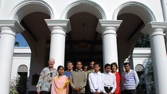 In this photo taken Nov. 29, 2012,  guests and staff members pose at the entrance of Thengal Manor, gracious home of the Barooah tea dynasty which is now open to tourists in Jorhat, India. Guests enjoy superb service from a staff of 15 for only five rooms. (AP Photo/Denis Gray)