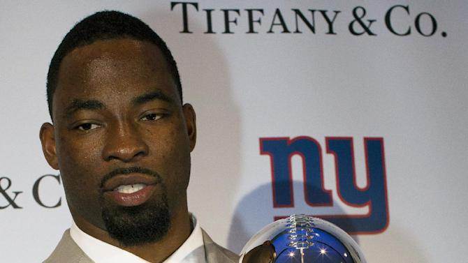 New York Giants defensive end Justin Tuck poses for pictures with the Super Bowl XLVI trophy and ring during a ceremony at Tiffany & Co., Wednesday, May 16, 2012, in New York. The Giants defeated the New England Patriots 21-17 in NFL football's Super Bowl XLVI to attain their fourth championship in franchise history. (AP Photo/John Minchillo)