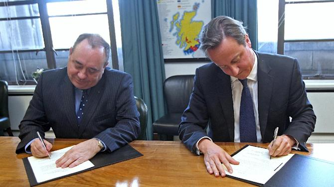Britain's Prime Minister David Cameron, right, and Scotland's First Minister Alex Salmond, sign a referendum agreement during a meeting at St Andrews House in Edinburgh, Monday, Oct. 15, 2012. Cameron met with the leader of Scotland's separatist administration Monday to sign a deal on a referendum that could break up the United Kingdom. Officials from London and Edinburgh have been meeting for weeks to hammer out details of a vote on Scottish independence. Sticking points included the date and the wording of the question. (AP Photo/Gordon Terris, Pool)