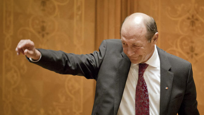 Romanian President Traian Basescu waves after his final speech in the country's parliament prior to a vote to impeach him in Bucharest, Romania, Friday, July 6, 2012.  The governing coalition has vowed to go ahead with a vote to impeach President Traian Basescu, as the European Union expressed concern about Romania's rule of law. Parliament voted to suspend Basescu and a referrendum on his impeachment will take place on July 29, 2012. (AP Photo/Vadim Ghirda)