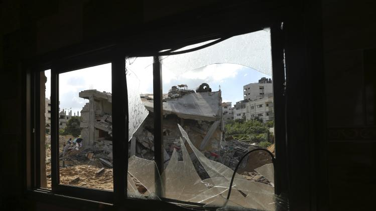 A house which police said was destroyed in an Israeli air strike is pictured through a neighbouring damaged house in Gaza City