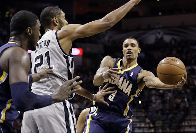 Indiana Pacers' George Hill (3) passes around San Antonio Spurs' Tim Duncan (21) to teammate Roy Hibbert, left, during the first half on an NBA basketball game Saturday, Dec. 7, 2013, in San A