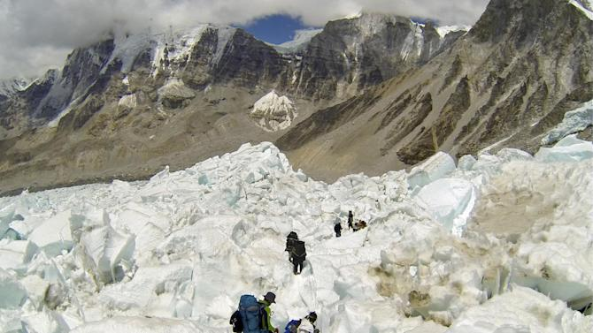 FILE - In this May 22 2013 file photo, climbers descend Khumbu Icefall on their way back to Base Camo after summitting the 8,850-meter (29,035-foot) Mount Everest. With its dreams of covering a daredevil's attempt to jump off Mount Everest over, the Discovery network is instead making a documentary on the avalanche, Friday, 18, 2014, that killed more than a dozen mountain guides. Discovery President Eileen O'Neill said Tuesday, April 22, the network hopes to air the film within the next few weeks. Discovery will encourage viewers to donate to a relief fund for families of the Sherpa guides killed in the disaster. Several of the Sherpas killed were helping prepare for American Joby Ogwyn's planned jump from the summit in a wingsuit. Discovery planned to show the stunt on live television May 11.(AP Photo/ Pasang Geljen Sherpa, FIle)