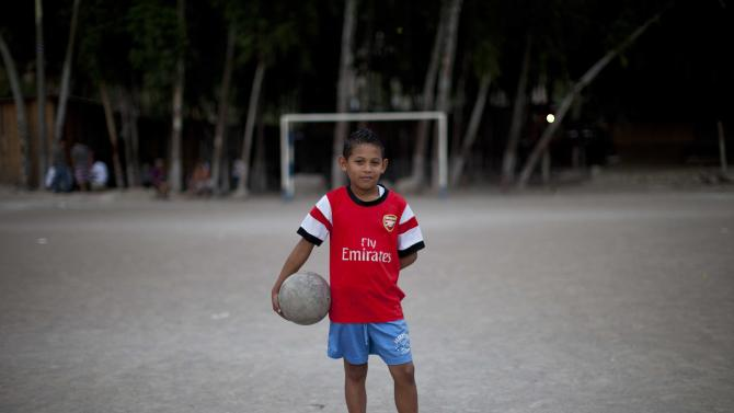 """In this Monday, March 3, 2014 photo, 11-year-old Maynor Ayala holds a soccer ball as he poses for a portrait before practice at his neighborhood's pitch in Progreso, Tegucigalpa, Honduras. Maynor allows himself to imagine going all the way to the World Cup one day, just like one of his heroes, Emilio Izaguirre, who will play in Brazil this summer on the Honduran national team. """"I want to be a soccer player,"""" Maynor says. (AP Photo/Dario Lopez-Mills)"""