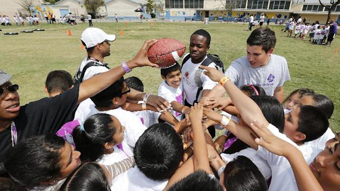 IMAGE DISTRIBUTED FOR NFL PLAYERS - Buffalo Bills wide receiver Marquise Goodwin huddles up with the kids during the NFLPA Rookie Premiere One Team/One Community Event at Sunrise Elementary School on Thursday, May 16, 2013 in Los Angeles. (Ric Tapia/AP Images for NFL PLAYERS)