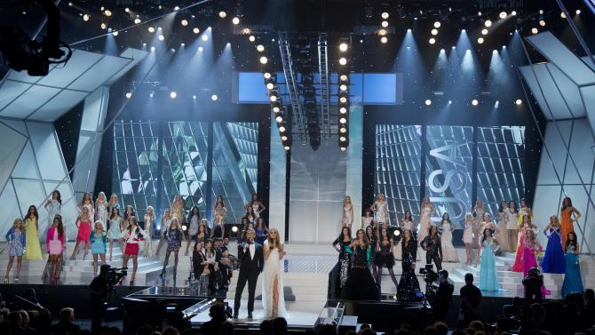 Andy Cohen, center left, and Giuliana Rancic open the 2012 Miss USA pageant, Sunday, June 3, 2012, in Las Vegas. (AP Photo/Julie Jacobson)