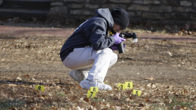 Law enforcement officers gather evidence at a Topeka home where a man suspected of fatally shooting two police officers had stayed after the crimes, in Topeka, Kan., Monday, Dec. 17, 2012. A suspect in the killings is dead after a nearly two-hour armed standoff, authorities said Monday. (AP Photo/Orlin Wagner)